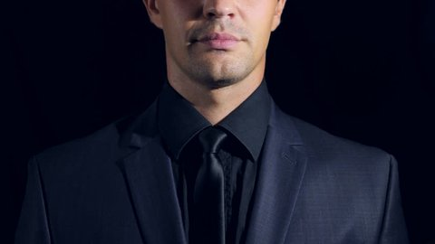 super close-up of a man in black clothes on a black background. 4k. Slow motion. man sends an air kiss to the camera and smiles