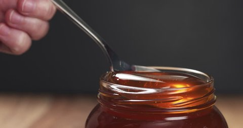 Slow motion honey pour from spoon in glass jar