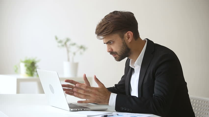 Annoyed angry businessman troubled with sudden computer failure, stressed man having problem with broken pc using laptop, pressing keys on hanging device, leaving workplace unable to fix gadget