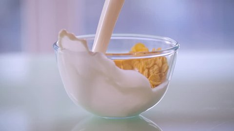 Milk pouring into a bowl of cereal cornflakes HD close-up slow-motion video. Corn flakes and milk splashing. Morning breakfast food