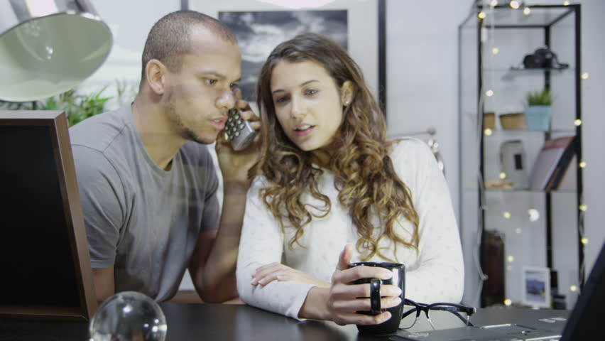 An attractive young couple take a telephone call together and receive some good news. They celebrate by kissing and hugging each other. In slow motion.
