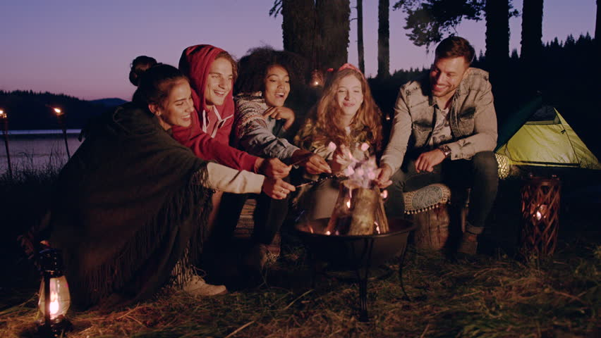 Attractive Multiracial Group Of Young Friends Sitting Around Bonfire At Dusk In Forest Laughing And Holding Marshmallows Hiking Lifestyle Happiness In Nature Concept Slow Motion Shot On Red Epic W 8k #30848416