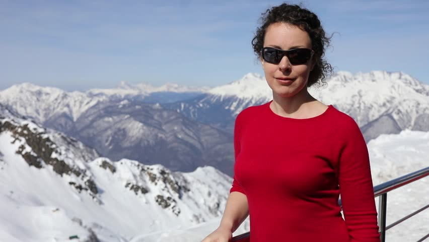 Woman in red dress stand and remove sunglasses near mountain landscape at sunny day, slow motion.