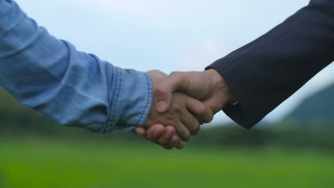 Farmer And Businessman Shaking Hands On Green Rice Fields
