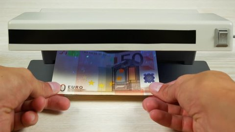 Authentication of money on the detector. Banknote denomination of 50 euros under the lamp of the detector.