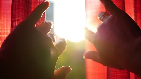 The girl opens red curtains and played with his hands through the sun's rays. Hand closeup