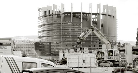 STRASBOURG, FRANCE - CIRCA 2016: Large construction site with European Parliament Headquarter building in Strasbourg in the background with Liebherr excavator working black and white