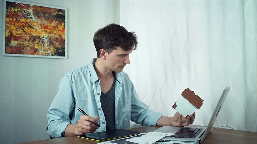Freelancer designer sketching on tablet housing project using laptop, holding model of house in his hand. Young guy working at home office. Modern abstract picture at wall behind | Shutterstock HD Video #30910315
