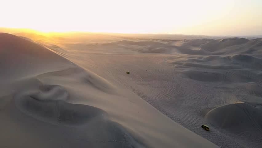 Aerial drone footage on a sunny day above sand dunes of Peru. Close to Ica and Huacachina. Similar to Sahara and Emirates Deserts. Boogie cars driving and people sandboarding. Color Corrected. #30910486