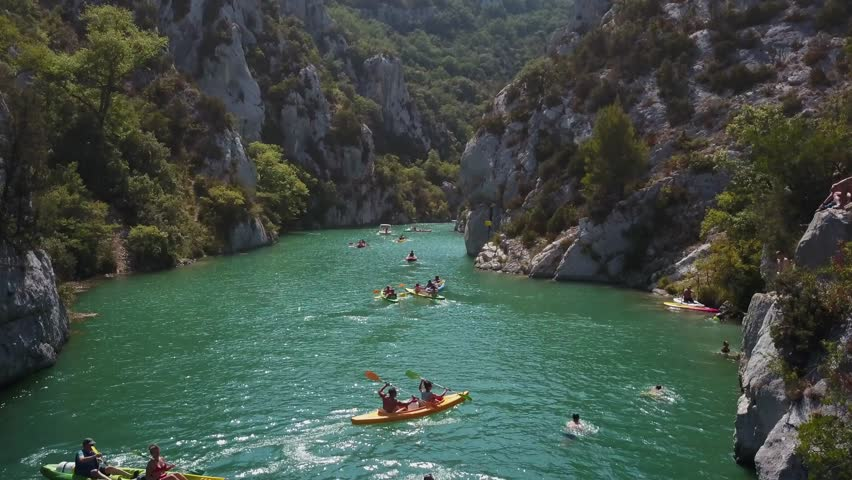 Aerial view of kayaks in a river canyon of Gorges du Verdon, France. View of kayaking and swimming in Verdon Gorge in the summer sunshine. 4k drone footage of rocky canyon landscape teal blue water.