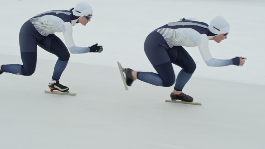 Tracking with slow motion of professional female speed skaters wearing spandex full-body covering suits sprinting along track in ice rink