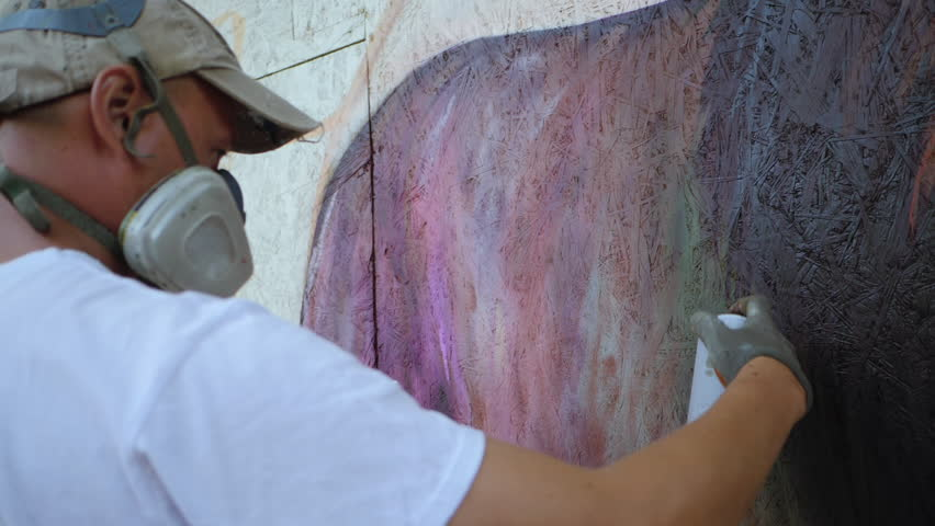 Street artist painting colorful graffiti on generic wall - Modern art concept with urban guy performing and preparing live murales with red aerosol color spray. Slow motion. | Shutterstock HD Video #30926749