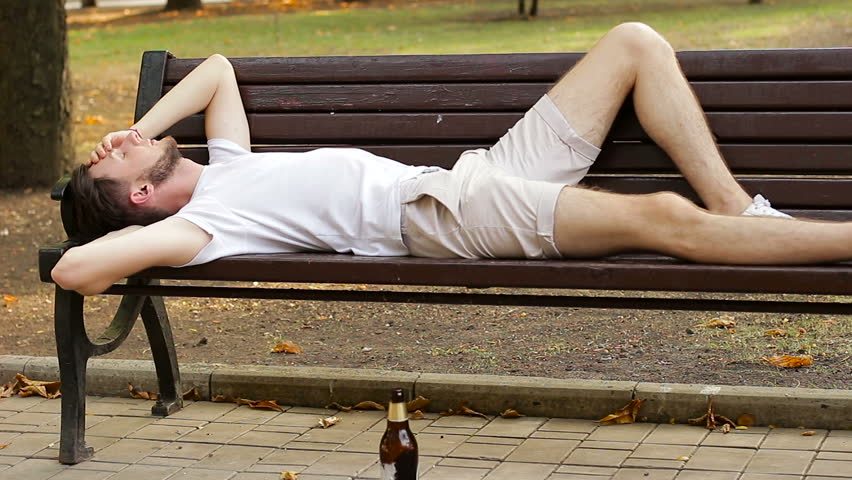 Teenager lying on a bench drunk. He reaches for the bottle and drinks beer. Alcoholism and addiction