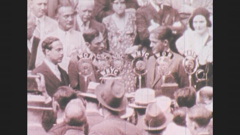 1930s: Mayor of New York makes speech into radio microphones next to honorary golf player, Bobby Jones before crowd. People clap.