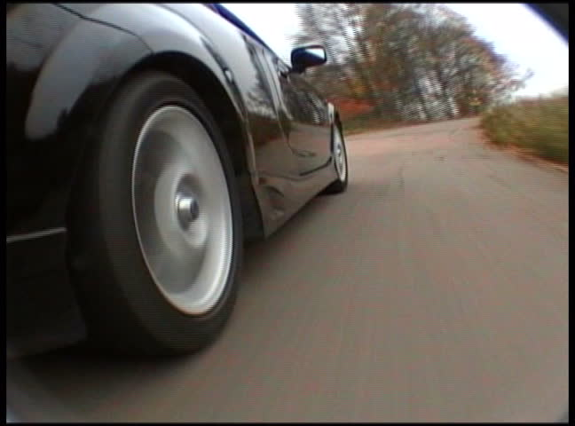 Black sport car in motion by the road. View from on-board camera on weel and wing