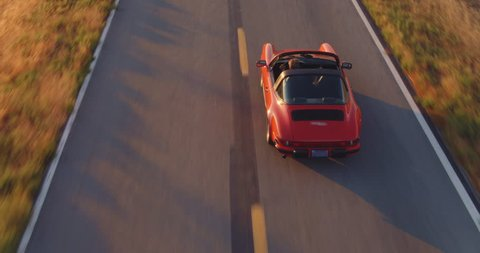 Aerial View Of Happy Couple Driving Vintage Convertible Sports Car Down Country Road At Sunset