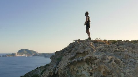 Man jogging on an island stops on top of a cliff in front of the ocean and exults