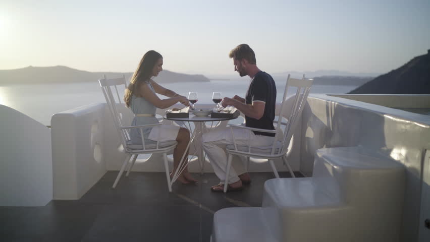 4k travel video honeymoon couple eating burger with salad on romantic terrace outside on santorini island high up the caldera