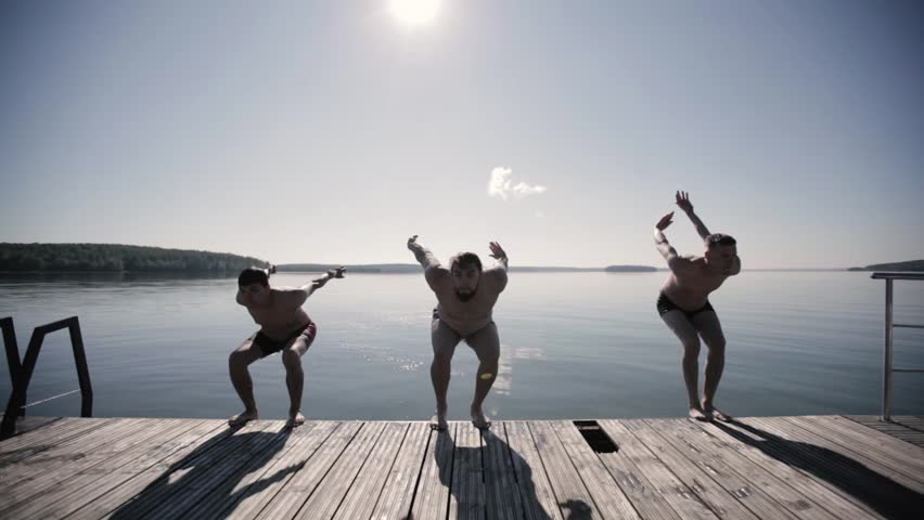 Three guys do a somersault with their backs forward jumping into the water
