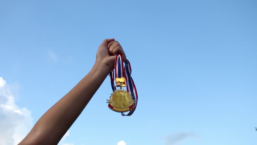 Winners success award concept : Blurred of hands raised and holding gold medals with Thai ribbon against blue sky background to show team success in business
