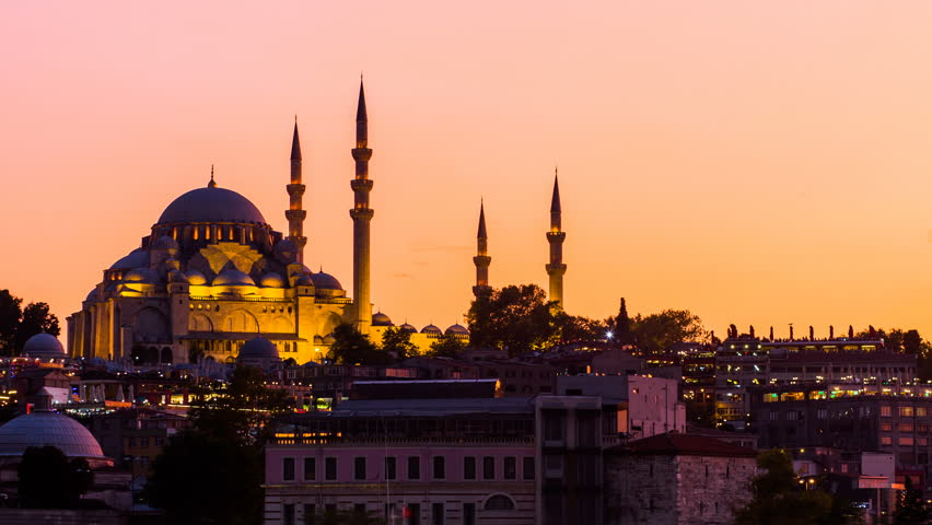 Zoom out Timelapse view of Suleymaniye mosque with tourist ships floating at Bosphorus in Istanbul at night