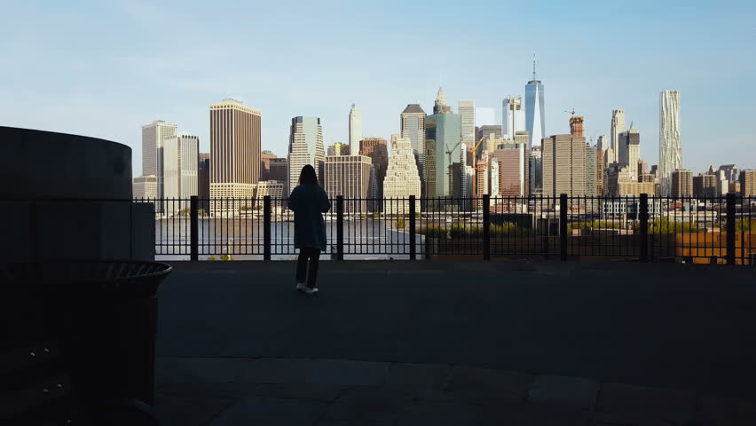 Aerial view of young woman standing on the pier in Brooklyn park, drone flying to Manhattan in New York, America. | Shutterstock HD Video #31039345