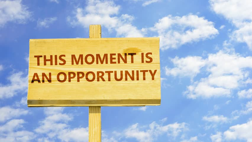 This moment is an opportunity. Words on a wooden sign against time lapse clouds in the blue sky.
