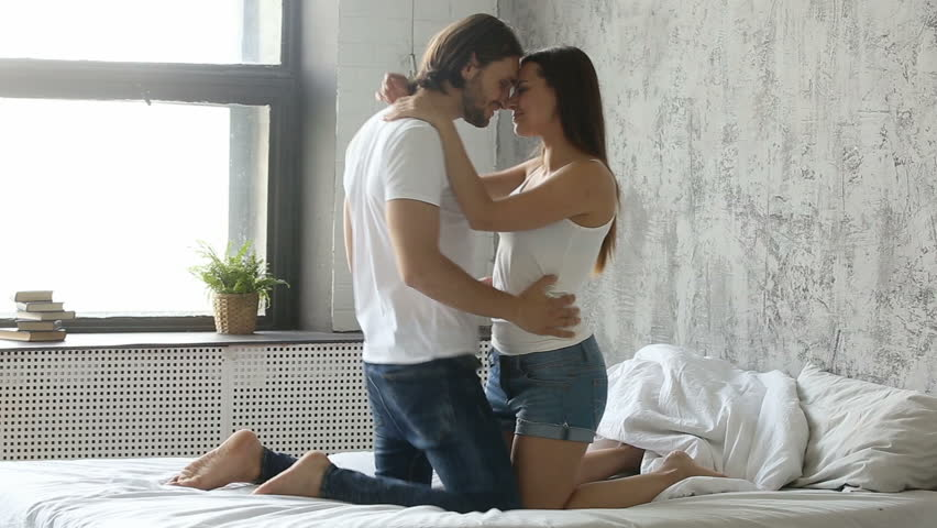 Young passionate hot couple kissing and hugging while undressing each other in bed, sensual lover taking off clothes of sexy hot desirable woman turning on foreplay before having sex or making love