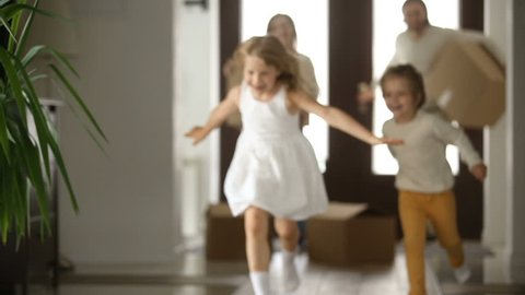 Excited kids boy and girl running into new home with parents holding boxes at background, happy couple with children and packed cardboards just moved in big modern house, family relocating concept