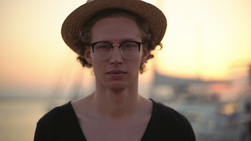 Attractive young man in straw hat, glasses closeup against sea sunset lighting. Slow motion