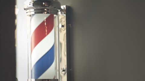 Barber pole rotating on wall in hairdresser shop. Barber pole spinning at barbershop. Vintage barbershop and hairdresser symbol. Traditional barber pole rotating in barbershop