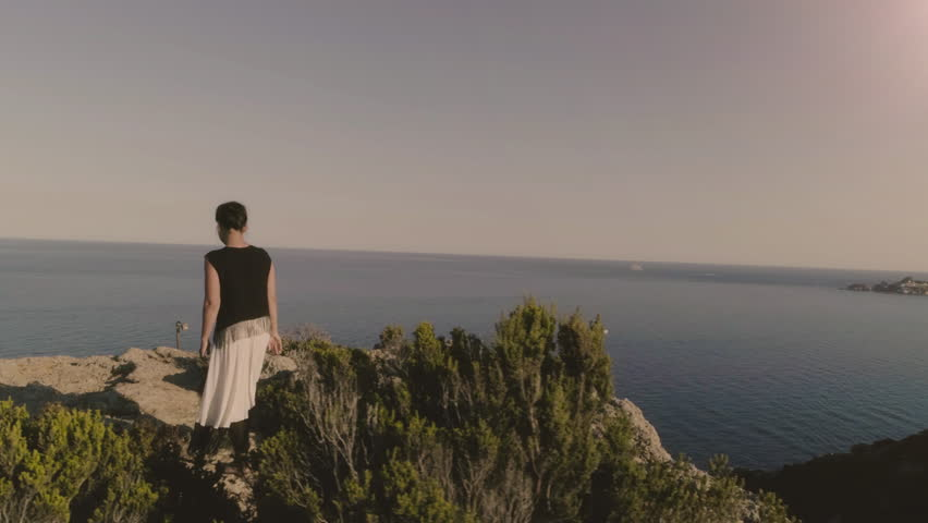 Young woman standing on top of a cliff on an island looking at the ocean | Shutterstock HD Video #31090726