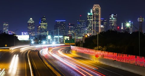 Dallas Skyline at Night Time-lapse. a time-lapse of the Dallas, Texas skyline at night with traffic light streaks on the highway and buildings in the background