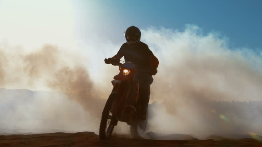Professional Motocross FMX Motorcycle Rider Drives Through Smoke and Mist Over the Dirt Road Track. Shot on RED EPIC-W 8K Helium Cinema Camera.