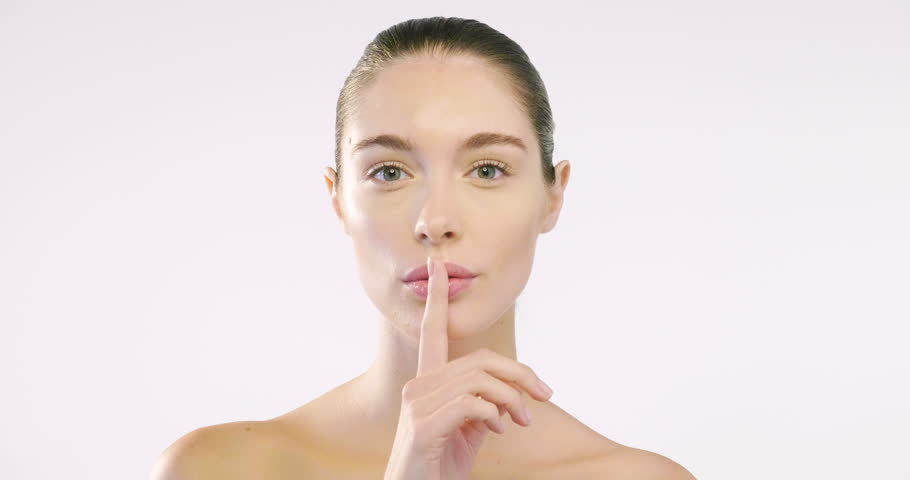 Close up of the face of a beautiful girl with perfect skin and clean from all impurities and with her finger in front of her mouth it is a sign of silence. Concept of beauty secrets and creams. | Shutterstock HD Video #31130956
