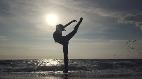 Young woman in casual style - denim and black top doing ballet at the beach. Attractive ballerina practices in stretching on sandy coastline in autumn. Slow motion.