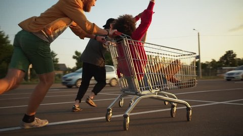multiethnic friends entertaining in mall parking lot in bright day. energetic guys circling attractive cheerful girls in shopping cart enjoying free time slomo