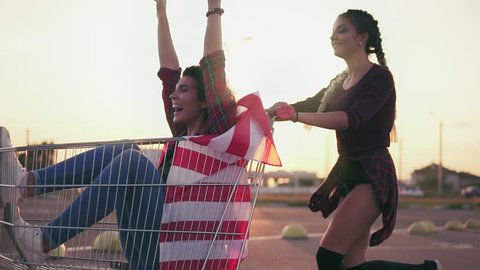 Young hipster teen girls having fun at the shopping mall parking, riding in shopping cart holding the american flag. Lens flare. Slowmotion shot