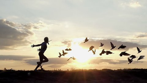 a Happy Young Man Runs Quickly and Frightens Doves, Which Take Off in a Mountainous Area in Eastern Europe at Sunset in Slow Motion. the Man Puts Hands Aside and Looks Cheerful .