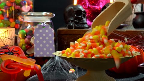Happy Halloween trick or treat party table with bowls and apothecary jars of candy with skull candles against a black background, scooping candy close up.
