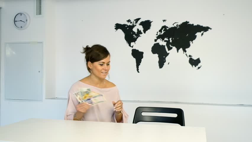 Young teacher using interactive whiteboard to display the world young woman sitting at the table on the background of world map and holding cash in gumiabroncs Gallery