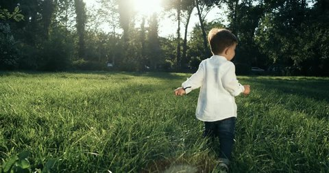 Cute baby boy with wite shirt running in grass field . Slow Motion. 4k. The camera behind the baby.