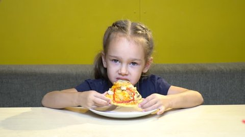 Little child girl portrait eat slice of pizza at cafe with yellow walls