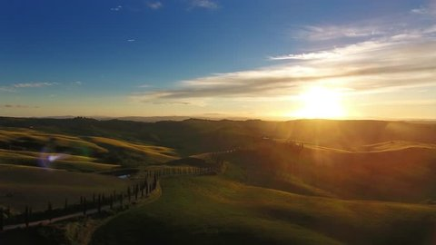 Tuscany aerial landscape with road and cypresses of farmland hill country at sunset. Italy, Europe, 4k