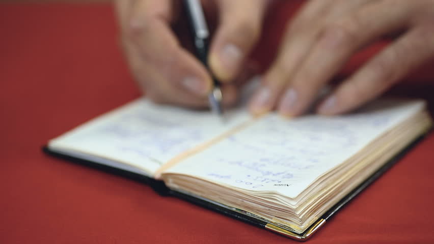 Businessman checking his handwritten to-do list making new notes and reminders