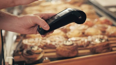 Close-up of woman making payment through NFC in bakery, cafe restaurant, mobile phone contactless pay for bill with terminal, banking