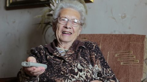 Old woman switches remote control TV channels on the couch at home
