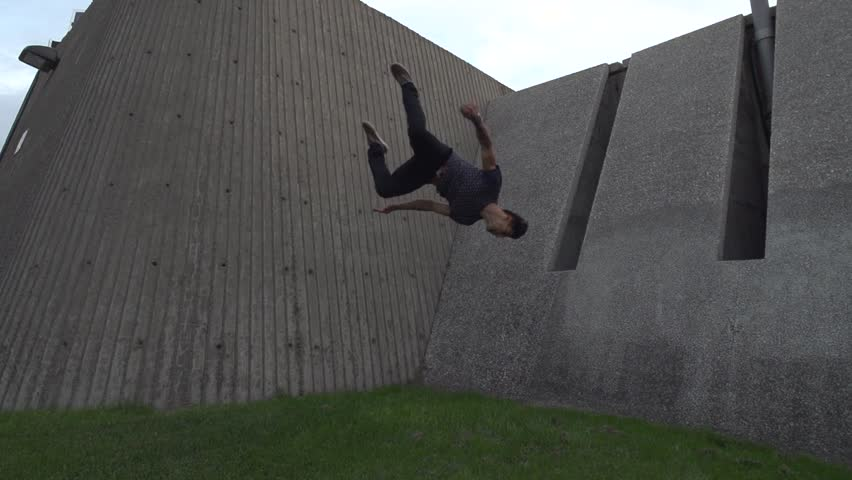Professional parkour dare devil does crazy difficult 2 step wall flip off of architectural angled walls. Close Angle. Shot in Slow Motion