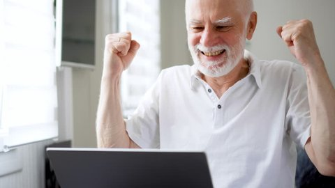 Handsome elderly senior man working on laptop computer at home. Received good news excited and happy. Remote freelance work on retirement, active modern lifestyle of older people. Success concept