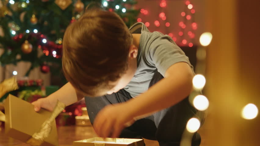 Close-up shot of an adorable little boy opening his Christmas present.